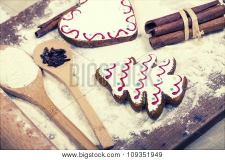 Christmas background with gingerbread cookies, spices and flour over wooden background