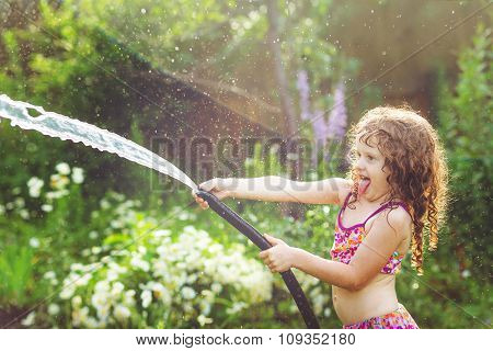 Happy Curly Girl Under Water Splashes In The Summer Garden.