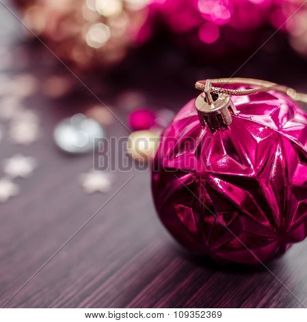 Magenta Christmas Ball On Bokeh Background Of Xmas Ornaments.