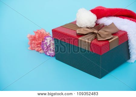 Present Box Covered By Santa Claus Hat With Carnation On Blue