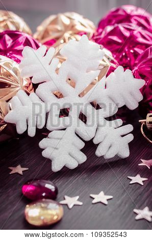 White Snowflake On Background Of Magenta And Gold Xmas Baubles.