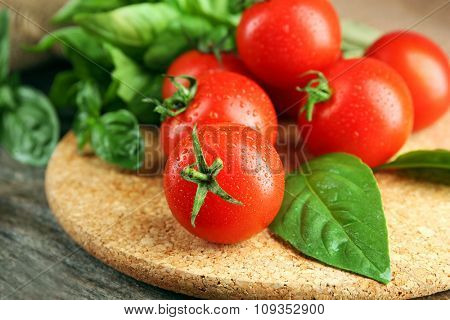 Cherry tomatoes with basil on wooden table close up