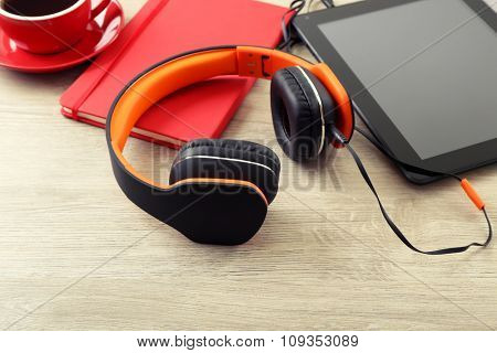 Headphones with tablet and notebook on wooden table background