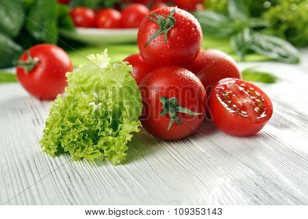 Cherry tomatoes with basil and lettuce on wooden table close up