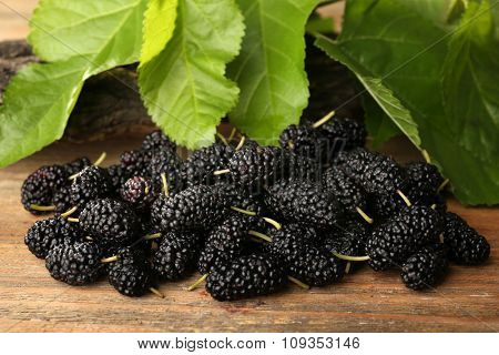 Heap of ripe mulberries with green leaves on table close up
