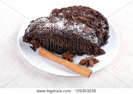 Delicious chocolate roll with spices in saucer on sackcloth background