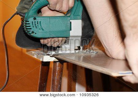 jigsaw, electric saw cutting plank