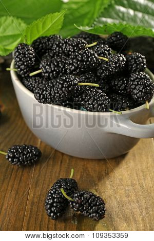 Ripe mulberries in bowl with green leaves on table close up