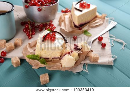 Tasty cheesecake with berries and cup of tea on table close up