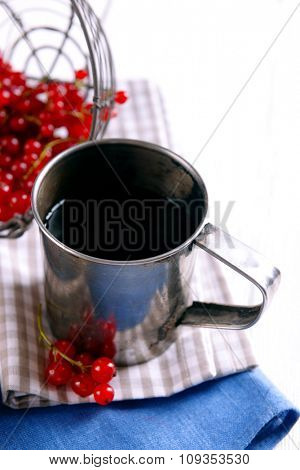 Cup of tea with berries on table close up