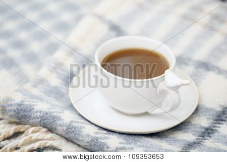 Cup of coffee on sofa in living room