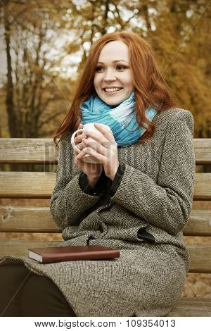 redhead girl with cup of tea sit on a bench in city park, fall season