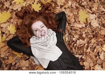 redhead girl lying on leaves and wink in city park, fall season