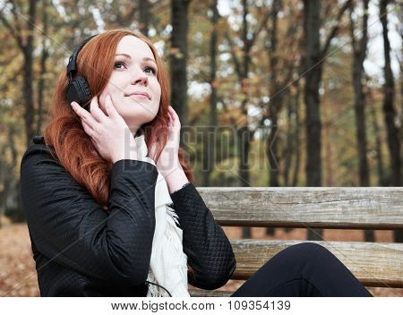 redhead girl with headphones listen music on player in city park, fall season