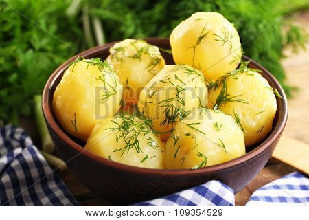 Boiled potatoes with greens in bowl on table close up