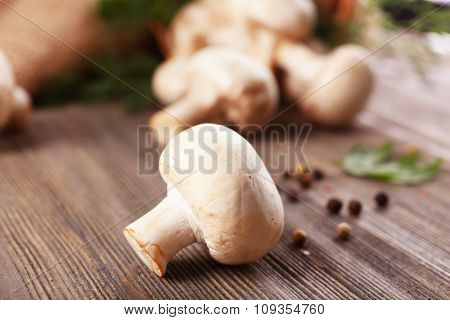 Champignon mushrooms and spices on grey wooden background