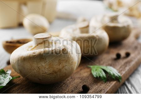 Champignon mushrooms, a spoon and spices on wooden table, close-up