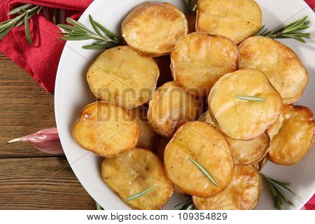 Delicious baked potato with rosemary in bowl on table close up