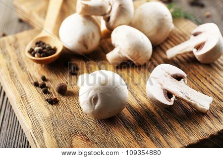 Champignon mushrooms, a spoon and spices on wooden background