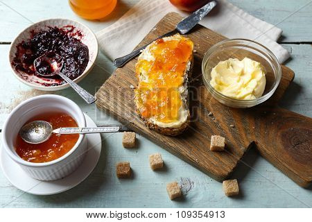 Tasty jam in the jar and bowls, butter, fresh bread and crackers on blue wooden background