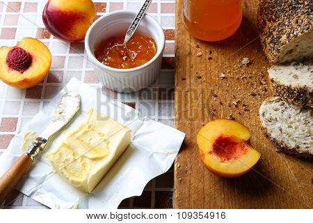 Tasty jam in the jar and bowl, ripe peaches, fresh bread and butter with knife on mosaic background close-up