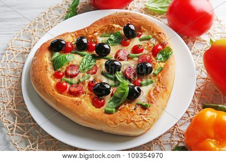 Delicious heart shaped pizza on the plate with vegetables around, close up