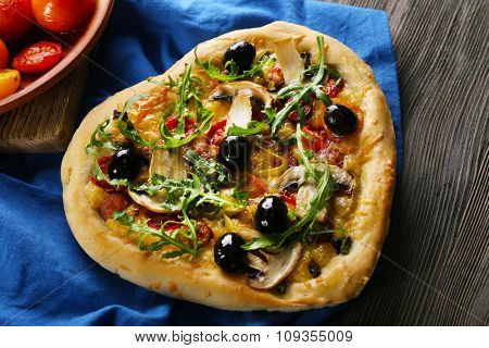 Heart shaped pizza on napkin on wooden table