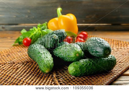 Composition of cucumbers, tomatoes and sweet peppers on wicker serviette against wooden background