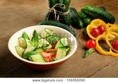 Vegetable salad with cucumbers on wooden background