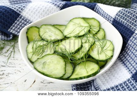 Sliced cucumbers on white plate with blue checked cotton serviette