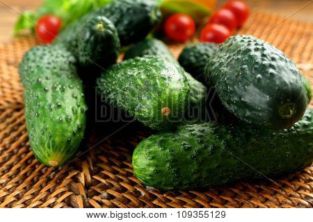 Composition of cucumbers, tomatoes and sweet peppers on wicker serviette against wooden background, close up