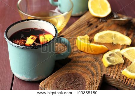 Mulled wine in a mug with citruses on wooden background, close up