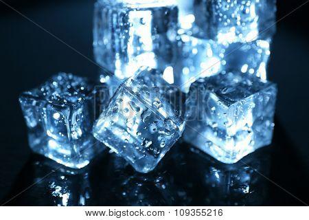 Shining ice cubes under blue light on liquid background