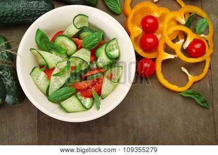 Vegetable salad with cucumbers and pepper on wooden background