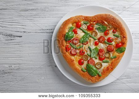 Delicious heart shaped pizza on wooden background