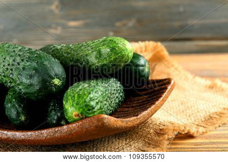 Fresh cucumbers in rustic bowl on  wooden background