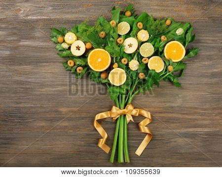Beautiful designed bouquet of fruits and vegetables on wooden background