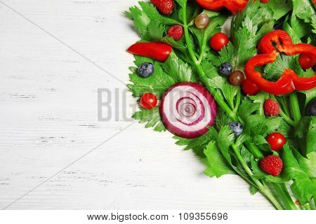 Cute bouquet of parsley and dill decorated with tomatoes, pepper and berries on light wooden background, close up
