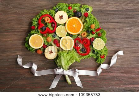 Beautiful bouquet of fruits and vegetables on wooden background