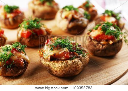 A wooden tablet with stuffed mushrooms on the table, close-up