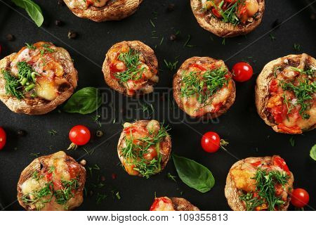 A frying pan with stuffed mushrooms and vegetables on the table, close-up, top view