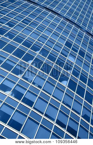 Windows of modern office building - architectural background. Toned in blue color
