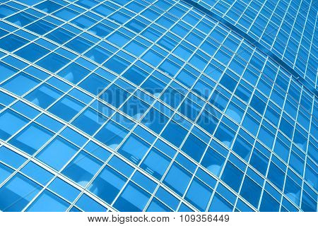 Windows of modern office building - architectural background. Toned in the blue color