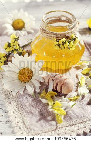 Honey and flowers on napkin closeup