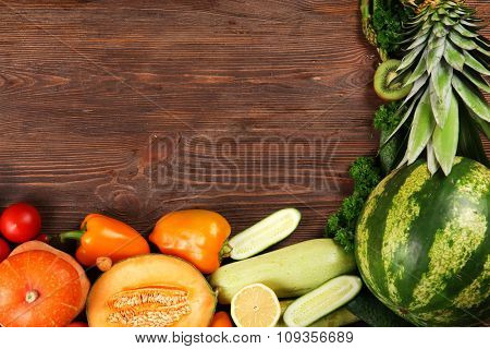 A frame made of bright fruit and vegetables on wooden background
