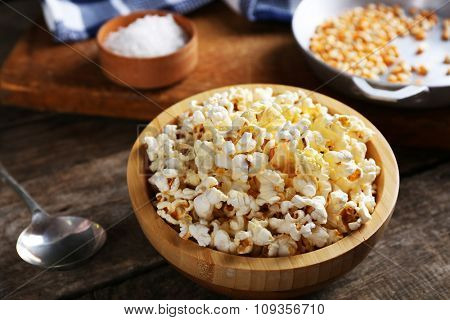 Salted popcorn in a bowl decorated with kitchen equipment on wooden table