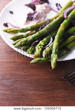 Fresh asparagus dish with red chopped onion on white plate against wooden background, close up