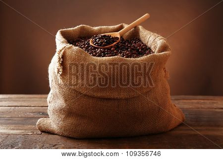 Sac with roasted coffee beans on wooden table in front of brown background