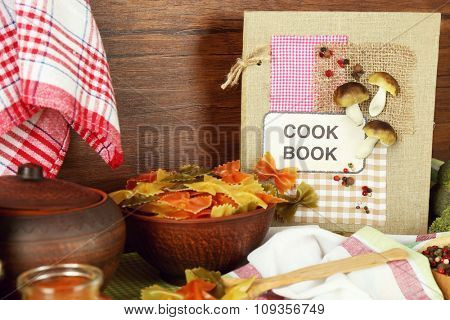 Decorated composition of cookery book and kitchen equipment on wooden background, close up