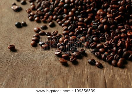 Aromatic coffee beans scattered on wooden background